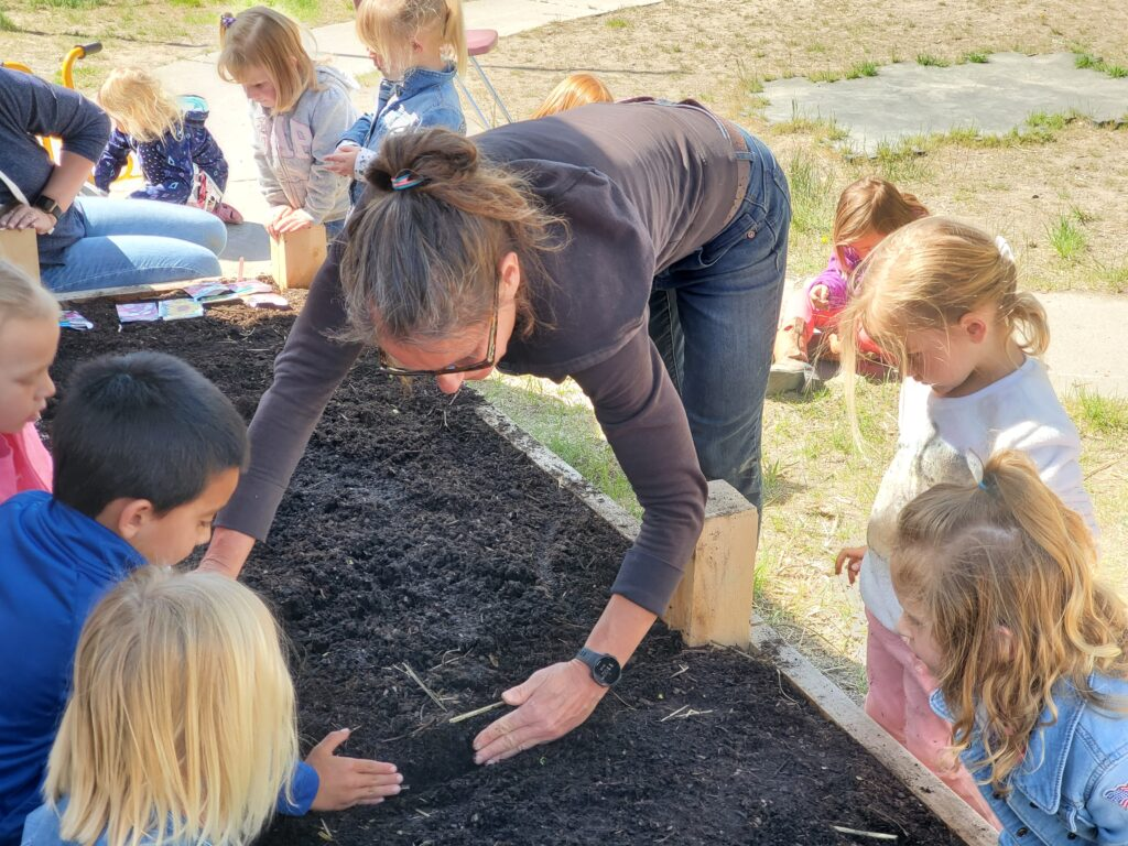 Modoc Harvest education coordinator, Jenny Kapp, engages in spring planting with Budding Tree students.